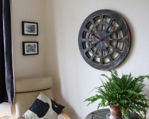 Große, zeitgenössische, 30 Zoll Holz-Skelett-Wanduhr - künstlerisch in erdigen Farben bemalt, einzigartiges Statetment-Design, in einem Wohnzimmer ausgestellt.
