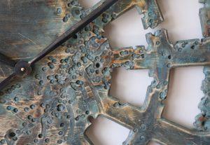 Ein Zoom auf die 100 cm große, zeitgenössische und dekorative Wanduhr – aus Holz handgefertigt und von hand bemalt, mit einmaligem ornamentalen Design.