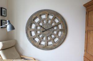 Aus Holz gefertigte Wanduhr als Prunkstück, 120 cm, mit runder Form und einzigartiger Zifferblattgestaltung.