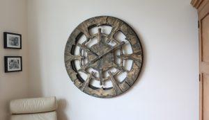 Riesengroße handgefertigte Wanduhr aus Holz, präsentiert im Wohnzimmer